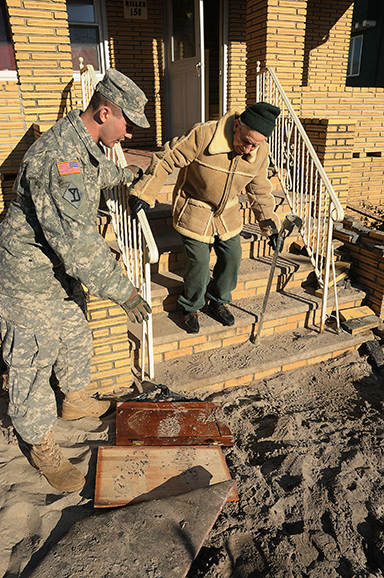 Spc. Joseph Pollini assists Leonard Miller down the steps of his boyhood home to a waiting vehicle in the Rockaway section of Queens, Nov. 6, 2012.