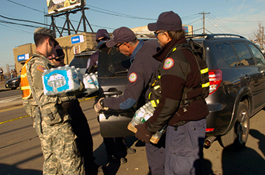 New York Army National Guard members distribute supplies to residents after Hurricane Sandy devastated the area.