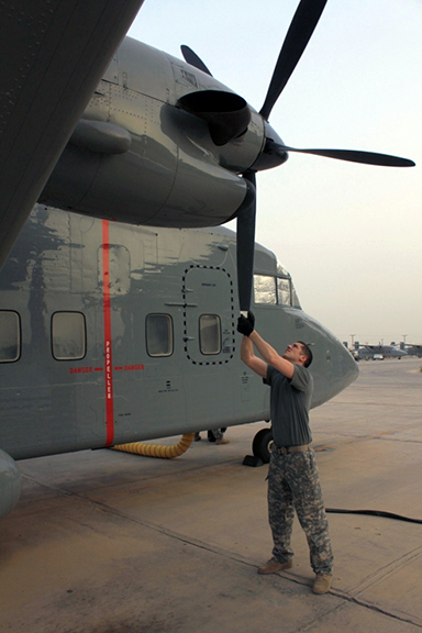 Sgt. Clint Walker, flight engineer with A Company, 641st Aviation Regiment, rotates the propeller of a C-23 Sherpa and checks it for damage and problems as part of his preflight checks and inspections.