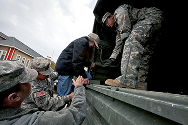 Soldiers assigned to Task Force South, New Jersey National Guard, assist a Long Beach Islander onto a M939 5-ton 6x6 truck during relief operations Oct. 31, 2012. The New Jersey National Guard is working with Long Beach Island civilian authorities in the aftermath of Hurricane Sandy.
