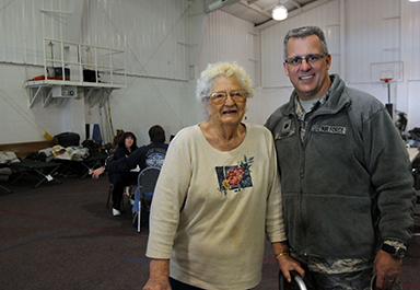 Maggie Selman of Craigsville, W.Va., stands with W.Va. Air Guard Lt. Col Yancy Short in the Summersville Baptist Church New Life Center, which operated as a shelter for the community during Hurricane Sandy. Selman was rescued by National Guard servicemembers after her power went out and snow blocked the road to her house. Short and other guard members helped return Selman to her home after hearing her storyabout being a Rosie the Riveter at the shelter.