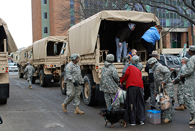 New York Army National Guard soldiers assist residents arriving by military vehicle to Long Beach City Hall for evacuation to shelters. Guard members are assisting throughout the flood-ravaged region.