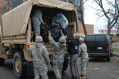 New York Army National Guard Soldiers from Company F, 427th Brigade Support Battalion, along with New York State Troopers, help residents arriving at Long Beach City Hall in Long Beach, N.Y., for evacuation to shelters.
