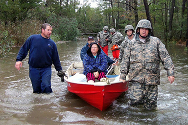 Virginia National Guard Soldiers transport citizens through high water to reach their medium tactical truck for evacuation on Cattail Road in the Mears, Va. area Oct. 30.