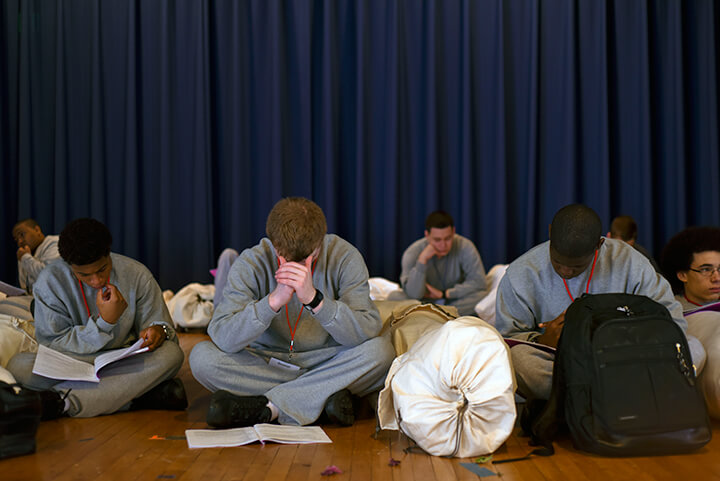 Candidates at the academy wait in a holding area with heads buried in their student handbooks.