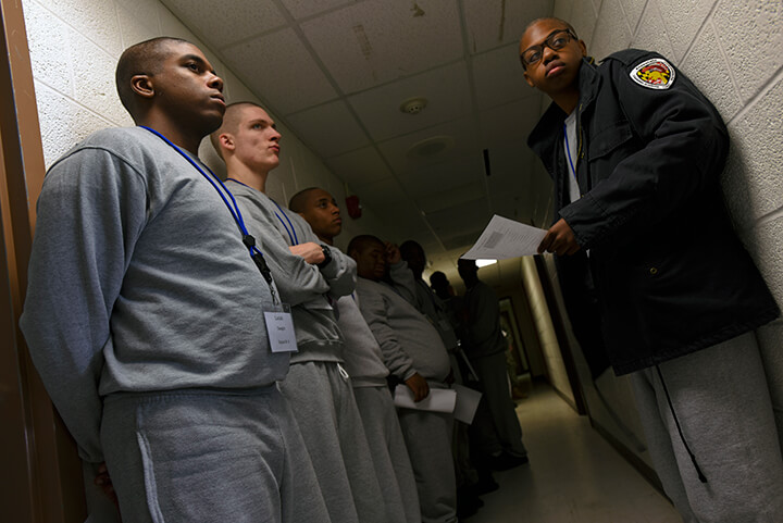 Candidates stand in a hallway after being issued their first uniform item- an academy coat.