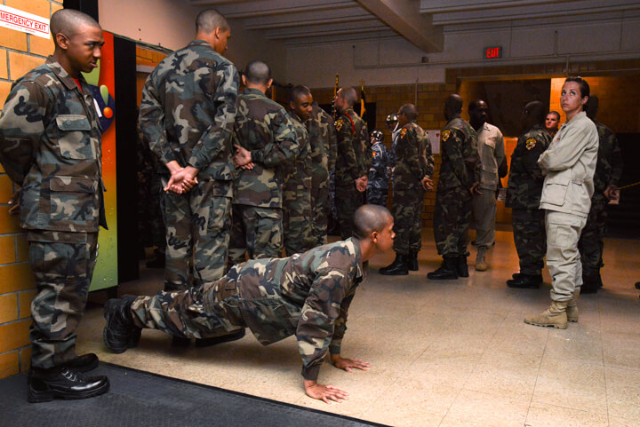 Malik Thompson knocks out pushups as Sgt. Drisana Lynch, right, a cadre member at the academy, keeps an eye on cadets while waiting for the start of graduation ceremonies. Graduation day doesn't mean a reprieve from the rules, or the consequences that come from ignoring a cadre member's instructions.