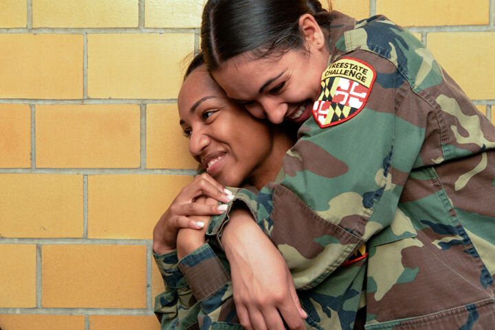 Excitement and emotions run high as Laneesha Johnson, right, shares a celebratory hug with fellow cadet Jada Estep as the two wait behind the scenes for graduation ceremonies to begin.