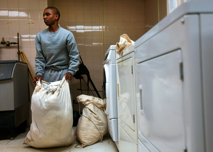 Tyshawn Delaine looks over full bags of dirty laundry as dryers hum in the barracks laundry room.