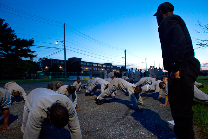 The glow of streetlights contrast against the pre-dawn sky as cadre members lead cadets in morning physical fitness training.