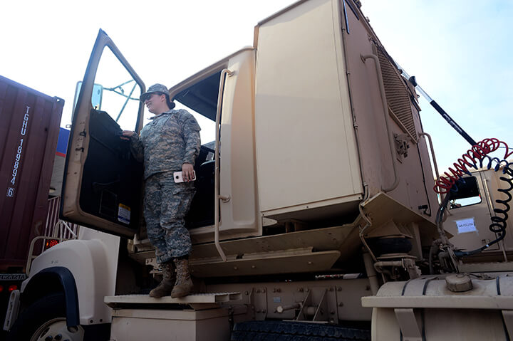 Spc. Michaela Schiesser steps out from the cab of her truck after pulling into a fuel stop.