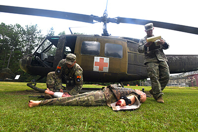 Staff Sgt. Matthew Ortiz (left), infantryman with the New York Army National Guard's Alpha Company, 1st Battalion, 69th Infantry Regiment, performs simulated first-aid on a mannequin during the casualty medical evacuation portion of the competition.