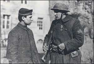 Sergeant J. Letzing, Company E, 104th Infantry (MA), 26th Division talks with his German prisoner