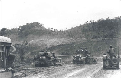 A bulldozer and 5-ton dump truck of the 116th Engineer Battalion