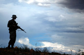 An Arizona National Guard Soldier stands watch on a ridge above Nogales, Ariz., at the U.S. border with Mexico in mid-July. Only those Guard troops whose mission may expose them to danger are armed for purposes for self-defense. The Citizen-Soldier is a member of Alpha Company, 1st Battalion, 158th Infantry, 29th Brigade Combat Team. (Photo by Sgt. Jim Greenhill, National Guard Bureau)
