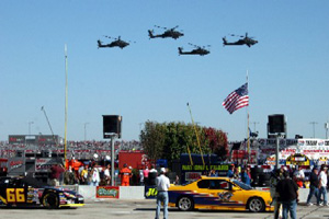 Four AH-64 Apache helicopters perform a flyover prior to the Dickies 500.